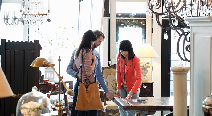 Young couple with a sales Assistant measuring a table they're contemplating buying in furniture store.