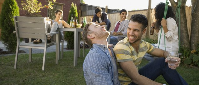 Group of friends enjoying drinks and laughs outside in the back yard.