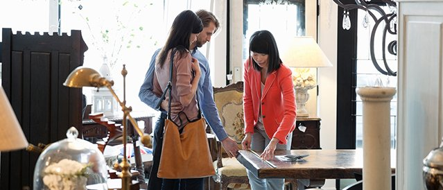 Young couple with a sales Assistant measuring a table they're contemplating at buying in furniture store.